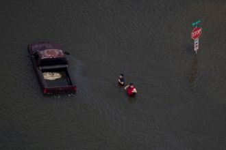 A woman holds her hands together as she and a man stand submerged in flood waters caused by Tropical Storm Harvey in Port Arthur, Texas, U.S. August 31, 2017. REUTERS/Adrees Latif