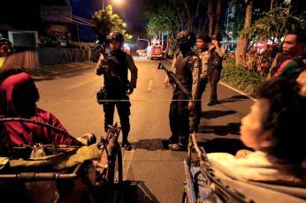 Residents stop near police line as Indonesian policemen guard at a street following a blast at the Pentecost Church Central Surabaya (GPPS), in Surabaya, Indonesia May 13, 2018. REUTERS/Beawiharta