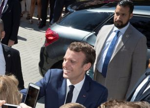 French President Emmanuel Macron, flanked by Elysee senior security officer Alexandre Benalla, greets supporters after having voted in the first of two rounds of parliamentary elections in Le Touquet, France, June 11, 2017. Picture taken June 11, 2017. REUTERS/Philippe Wojazer