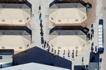 "Immigrant children, many of whom have been separated from their parents under a new ""zero tolerance"" policy by the Trump administration, are shown walking in single file between tents in their compound next to the Mexican border in Tornillo, Texas, U.S. June 18, 2018. Picture taken June 18, 2018. REUTERS/Mike Blake"