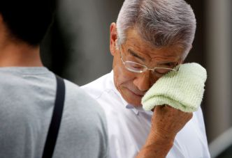 FILE PHOTO: A businessman wipes his face while walking on a street during a heatwave in Tokyo, Japan July 23, 2018. REUTERS/Issei Kato/File Photo
