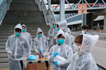 Residents wearing masks and raincoats volunteer to take temperature of passengers following the outbreak of a new coronavirus at a bus stop at Tin Shui Wai, a border town in Hong Kong, China February 4, 2020. REUTERS/Tyrone Siu